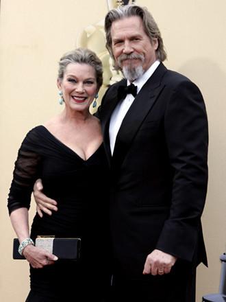Jeff Bridges, ganador al Mejor Actor, con un traje Gucci, con su mujer Susan Geston vestida con un Monique Lhullier